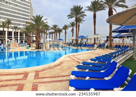 DEAD SEA, ISRAEL - DECEMBER 30, 2011: Winter in the Dead Sea. The picturesque pool and a comfortable high-rise hotel - stock photo