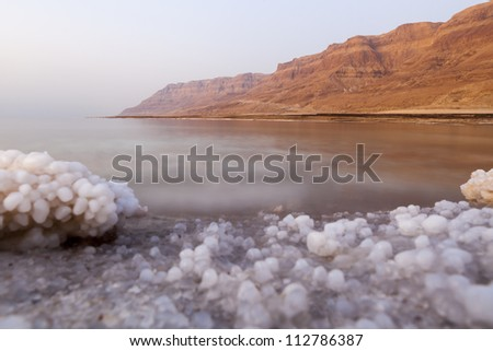 Dead sea landscape with minehral structures on the shore and desert mountains in the background - stock photo