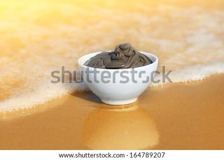 Dead Sea mud in a bowl on the seashore - stock photo