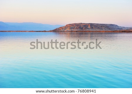 Dead Sea shortly before dawn, Jordanian mountains in the background. - stock photo
