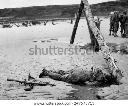 Dead U.S. soldier on Omaha beach on D-Day, June 6, 1944. Crossed rifles in the sand are a comrade's tribute. He was killed during the Normandy landings in Nazi occupied France, World War 2. - stock photo