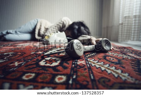 Dead woman on the floor, phone in the foreground - stock photo