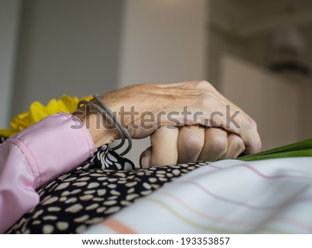 Dead woman with peacefully crossed hands holding flowers - stock photo