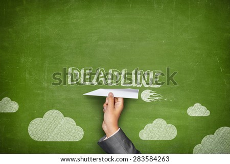Deadline concept on green blackboard with businessman hand holding paper plane - stock photo