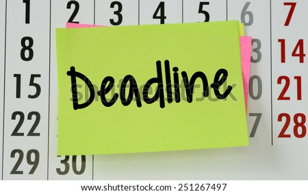 Deadline on calendar background. The phrase Deadline on sticky paper note stuck to a wall calendar background - stock photo