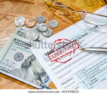 deadline time of 1040 tax form for 2016 with dollar and pen. Approved - stock photo