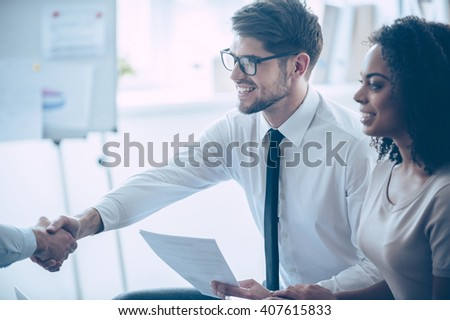 Deal! Close-up part of young handsome men shaking hands with smile while sitting at office with his coworkers  - stock photo