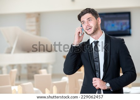 Deal on the mobile phone. Young and handsome businessman is talking on the mobile phone and smiling because of successful deal - stock photo