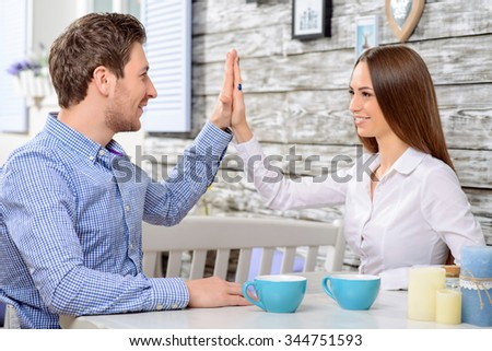 Deal. Positive content friends sitting in the cafe and  giving five to each other while spending great time in the cafe - stock photo