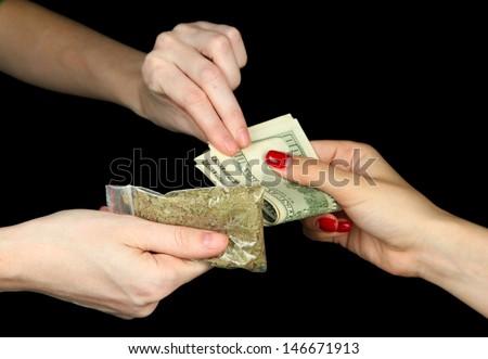 Dealer sells drug bag, isolated on black - stock photo