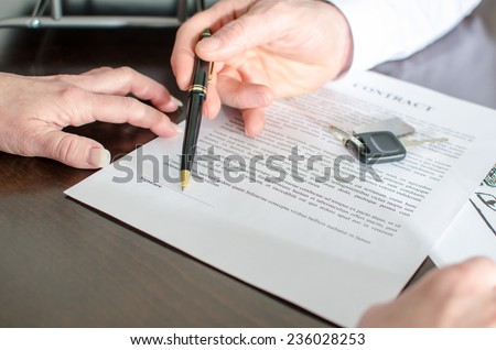 Dealer showing the signature place of a contract with his pen - stock photo