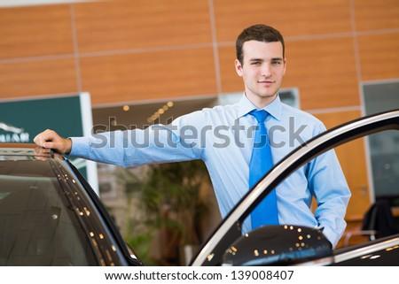 dealer stands near a new car, car dealerships - stock photo