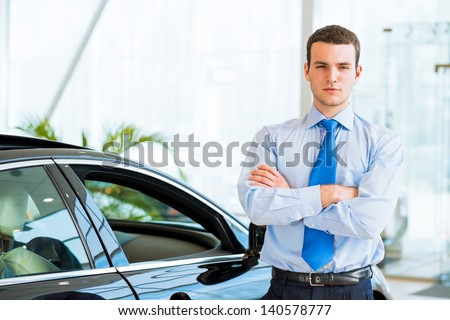 dealer stands near a new car in the showroom, folded his arms across his chest - stock photo
