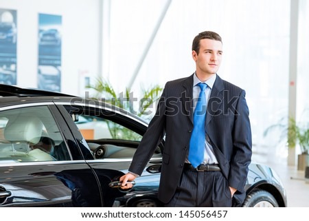 dealer stands near a new car in the showroom, put one hand on the car - stock photo