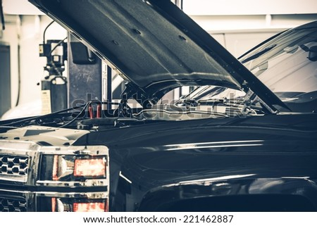 Dealing With A Dead Car Battery. Truck with Open Hood in the Auto Service Area Getting Jump. - stock photo