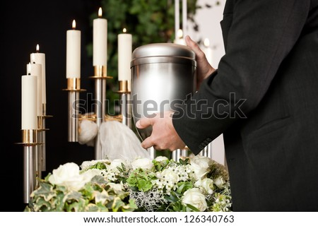 death and dolor  - funeral and cemetery, mortician carrying the urn to a bed of white roses - stock photo