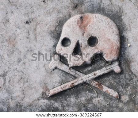 death head and cross bones on ancient tombstone, stone skull - stock photo