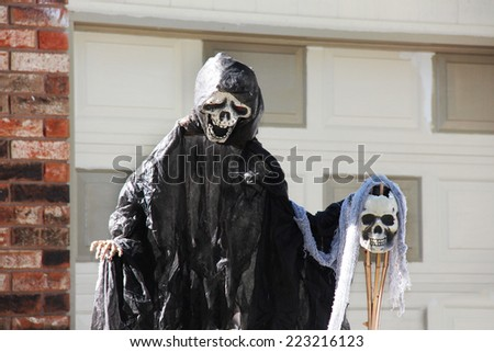 Death in a black hood and other scary Halloween decorations. - stock photo