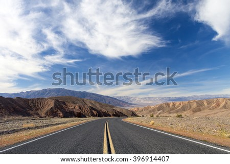 Death Valley desert roadway with blue sky. - stock photo