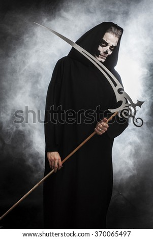 Death with scythe on black background and smoke - stock photo
