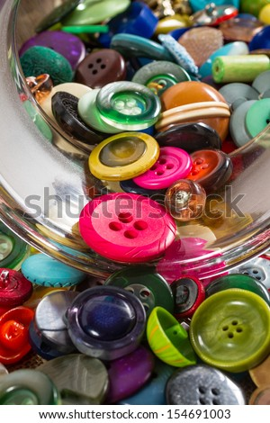 Deatil on a great variety of colorful vintage buttons spilling out of a jar, against a fabric background. Portrait orientation. - stock photo