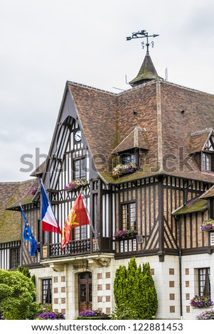 DEAUVILLE - JULY 18: Decorated with flags and flowers Town Hall (Mairie) in Deauville, France on July 18, 2012. Deauville Town Hall was restored in neo-Norman style in 1961 by Mayor Robert Fossorier. - stock photo