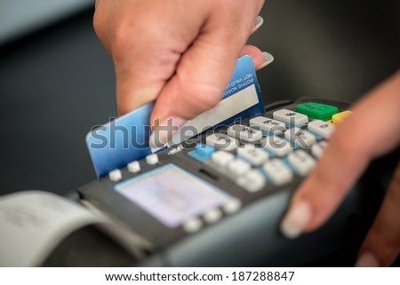Debit card swiping on card-reader device - stock photo