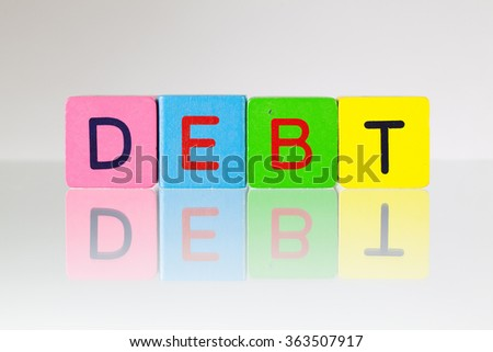 Debt - an inscription from children's wooden blocks - stock photo