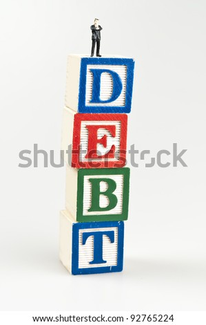 Debt word and toy business man - stock photo