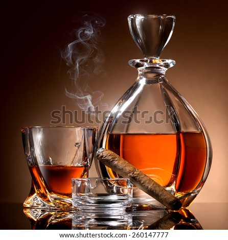 Decanter abd glass of alcohol and cigar on ashtray - stock photo
