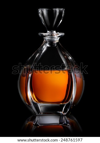 Decanter of cognac on a black background - stock photo