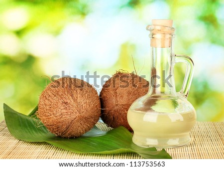 decanter with coconut oil and coconuts on green background - stock photo