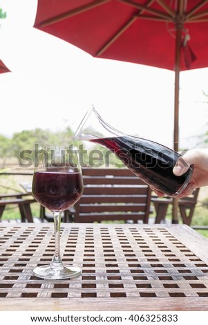 decanter with red wine and glass on abstract background of an outdoor nature scenery - stock photo