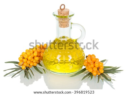 Decanter with sea buckthorn oil and berries isolated on a white background. - stock photo
