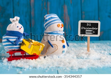 December 31 calendar day written on roadsign. Two snowman with gift, New Year concept. - stock photo