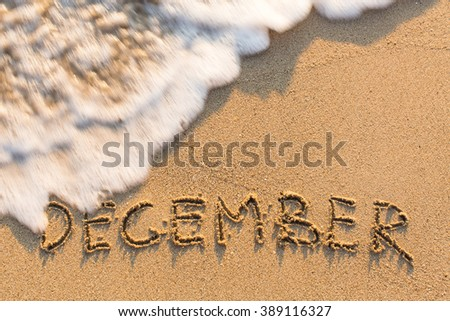 December - word drawn on the sand beach with the soft wave.  - stock photo