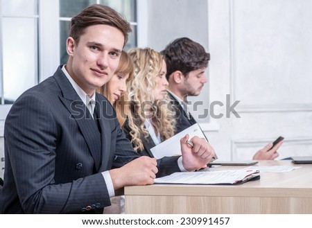 Decent work. Smiling businessman sitting at a desk and looking happily at the camera while his colleague businessmen talking in the background - stock photo