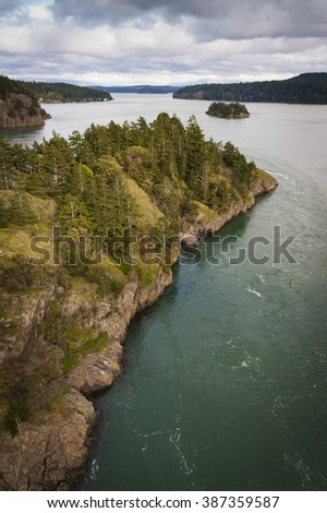 Deception Pass, Washington. Deception Pass is a strait separating Whidbey Island from Fidalgo Island, in the northwest part of the U.S. state of Washington. The current through here is very strong. - stock photo