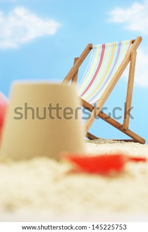 Deck chair behind and castle on beach - stock photo