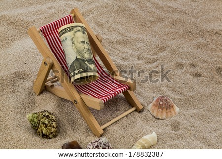 deck chair with dollars on the sandy beach. symbolic photo for travel costs, holidays, vacations. save on holiday - stock photo