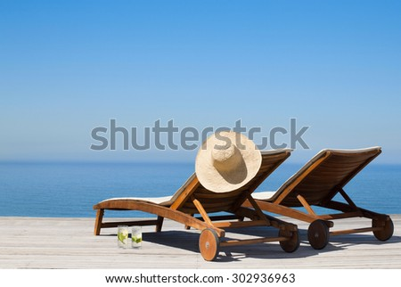 Deck chairs and infinity pool - stock photo