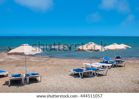 Deck chairs and parasols on a beach. Aegean Sea, Rhodes, Dodecanese Islands, Greece - stock photo