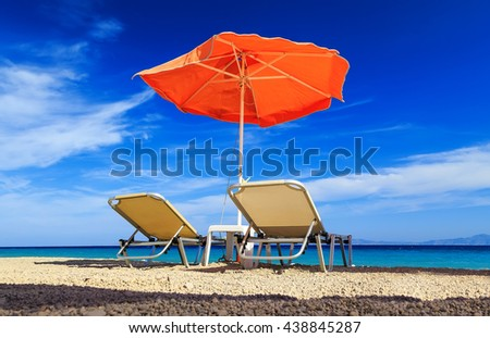 deck chairs and umbrella on a background of sea and pebbles - stock photo