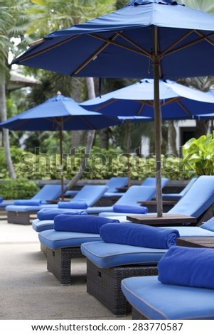 Deck chairs at a tropical resort in Thailand - travel and tourism image. - stock photo