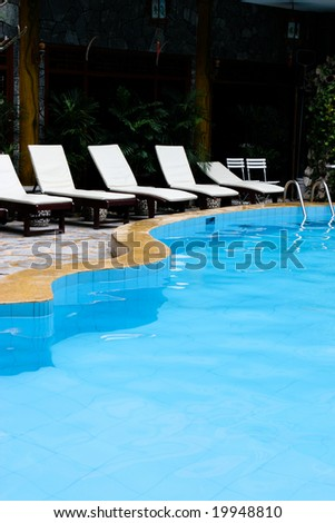 Deck chairs next to a swimming pool. - stock photo