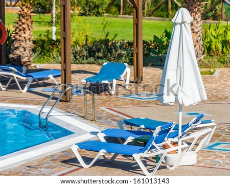 deck chairs under a canopy stand near the swimming pool - stock photo