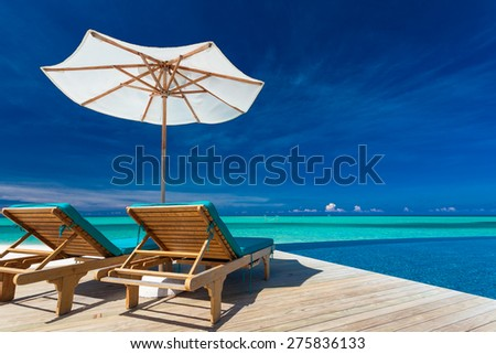 Deck chairs with umbrella overlooking infinity pool and tropical lagoon - stock photo