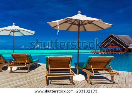 Deck chairs with umbrella overlooking infinity pool and tropical lagoon, Maldives - stock photo