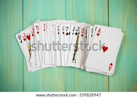 Deck of playing cards on blue wooden background - stock photo