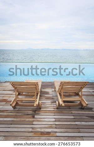 deckchair beside the pool and sea - stock photo